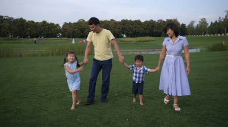 Joyful asian family walking holding hands in park