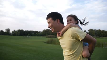 pigtail : Cute asian daughter on piggyback ride with her dad