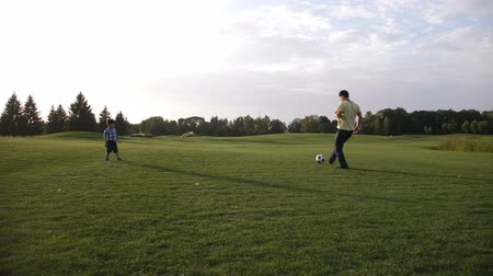 Asian toddler boy playing soccer with his father Stock Footage
