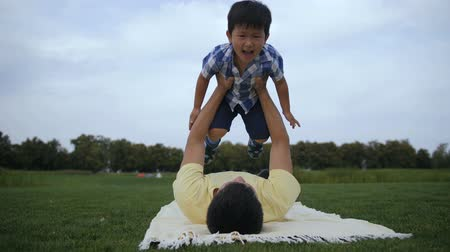 cobertor : Father and cute asian son enjoiyng leisure outside