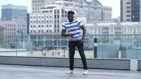 flexibility : Active black male dancing afrobeat style in city