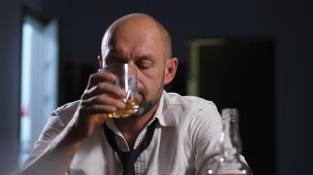 dismissal : Tired businessman releiving stress with alcohol