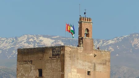 sierra nevada : Zoom out from Alhambra,  with waving flags and snow on Sierra Nevada in the background, Granada, Andalusia, Spain