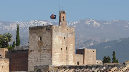 mouro : Zoom out from Alhambra,  with waving flags and snow on Sierra Nevada in the background, Granada, Andalusia, Spain