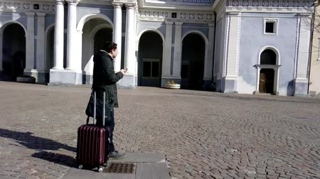 troli : Young tourist with red luggage checks the direction on his smartphone in front of a historic building and carries on walking on a cobbled square after finding the way