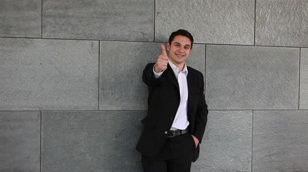 advokát : Happy business man on grey wall holding his thumbs up