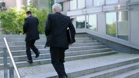 slomo : Two businessmen running up stairs in slow motion Stock Footage