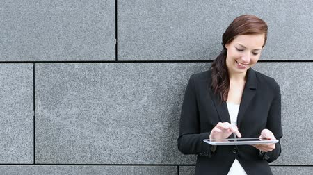 outside : Businesswoman with tablet PC leaning on a wall