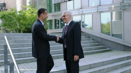 tratar : Two businessmen shaking hands after meeting on the stairway