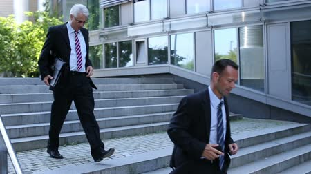 schody : Two business people running down stairs in slow motion