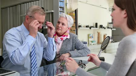 espetáculos : Senior man buying eyeglasses at optician retail store Stock Footage