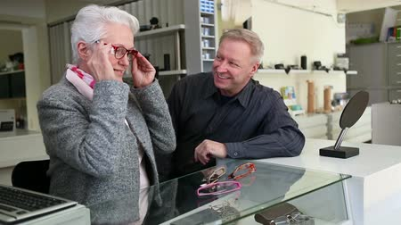 espetáculos : Optician helping senior woman customer finding new glasses in retail store