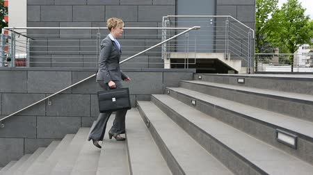 escada : Young businesswoman in a hurry walking stairs upstairs with briefcase