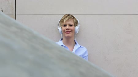 polegar : Young happy woman listening to music with with headphones and holding thumbs up