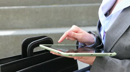 érintés : Hand of businesswoman using a tablet computer outside in a city