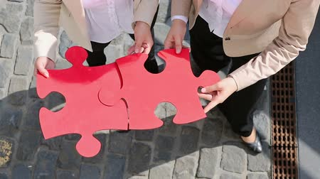 career success : Hands of two business women holding two oversized red jigsaw puzzle pieces