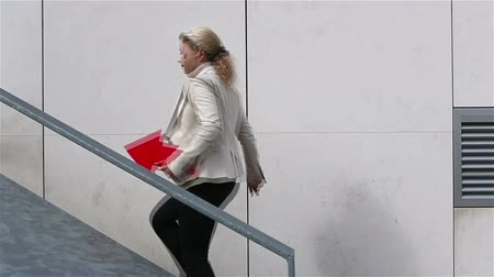 schody : Businesswoman running up stairs while holding a red arrow