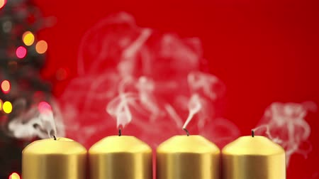 gyertyák : Blowing out four christmas candles after advent on a red background Stock mozgókép