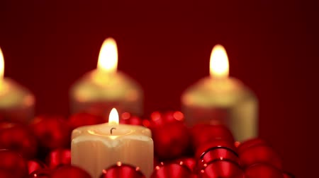 церковь : Candles burning in an arrangement of christmas ball ornaments on a red background Стоковые видеозаписи