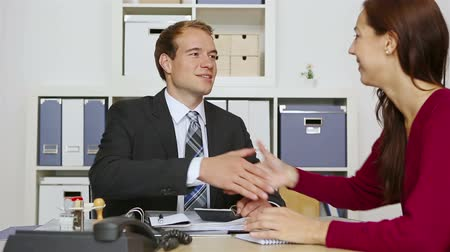 рукопожатие : Consultant shaking hands with woman in his office after a deal is made (Full HD) Стоковые видеозаписи