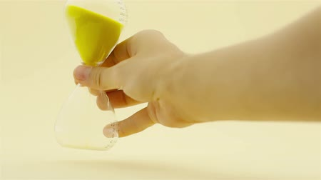 clock hands : Hand turning hourglass to measure time on yellow background (Full HD)