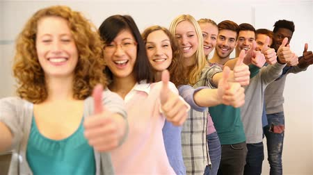dizilirler : Happy team of students holding their thumbs up (Full HD)
