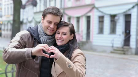 партнеры : Happy couple showing a heart with their hands outdoors (Full HD)