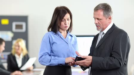 business man : Business man showing woman information on a smartphone in the office (Full HD)