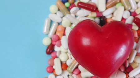 gyógyszerész : Pan view of a heart among many different medication pills and capsules (HD)