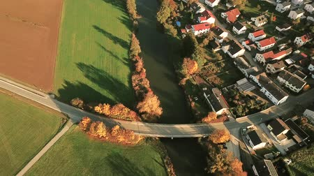 dava : Aerial pan shot of empty country road running over a road in autumn
