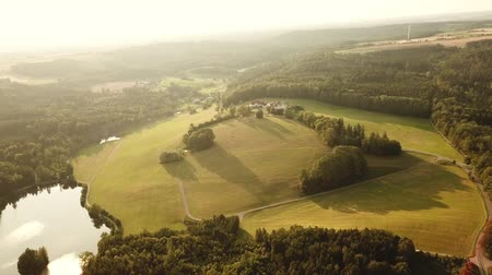 tracking : Aerial tracking shot of rural landscape with Haselbach reservoir lake in Bavaria, Germany and surrounding fields and forest (HD)