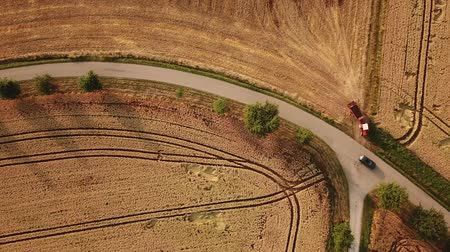 bajor : Birds eye tracking shot of red tractor leaving a field and touching another vehicle when entering a country road (HD) Stock mozgókép
