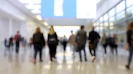 trade show : Blurred crowd of people walking through shot in one direction at a convention center hallway (HD)