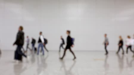 Blurred crowd of people walking in one direction in a hallway at a conference (HD)