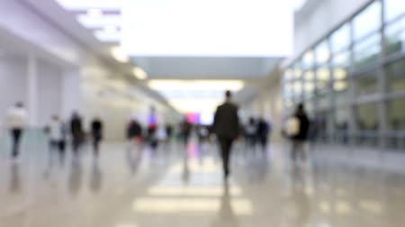 Blurred hallway of a conference center with people walking in one direction at a business convention (HD)