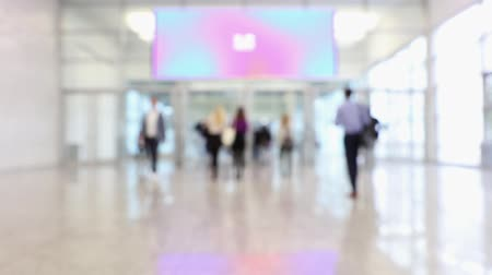 előcsarnok : Blurred people passing through in a convention hallway with a display area during a business conference (HD)