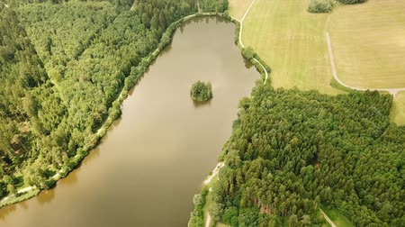 Aerial tracking shot of Haselbach reservoir lake with surrounding fields and forest in Bavaria, Germany (HD)