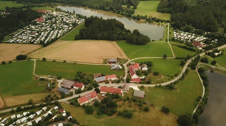 Aerial pan shot of rural landscape at Bavaria, Germany with settlement, camp site and hazelbach reservoir lake visible (HD)
