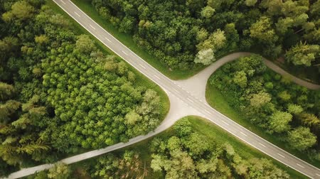 Rotating birds eye shot of empty country road junction in green forest during summer day (HD)