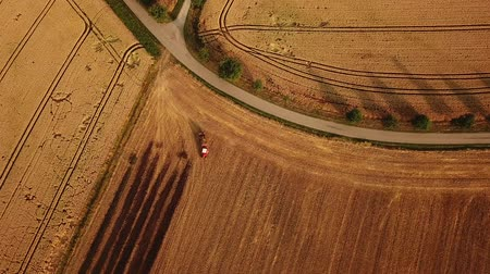 Birds eye still shot zooming in on little red tractor working on field during summer in Germany (HD)