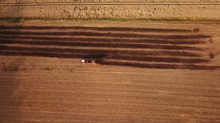 Birds eye still shot of a red tractor driving on a field during a summer in Germany (HD)