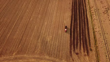 Aerial tracking shot of a red tractor driving in a field during Germany during summer (HD)