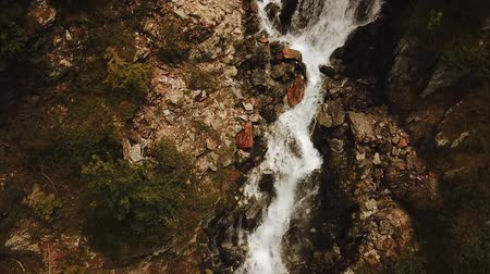 Tilt shot of wild water stream running over rocks in mountains in Rhône-Alpes region in France (HD)