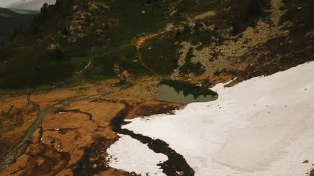 Aerial tracking shot of wild mountain landscape with snow and small lake in Rhone-Alpes region of France (HD)