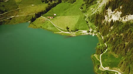 Cinematic aerial shot over turquoise mountain lake in Rhone-Alpes region of France in summer (HD)
