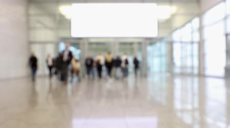Blurred crowd at convention passing through conference center hallway (HD)