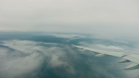 time journey : View of wing of plane, flying above the clouds, and then starting landing and flying under the clouds, Time Lapse
