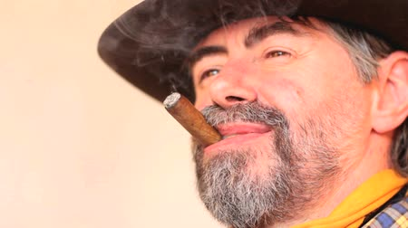 egyéniség : Closeup portrait of cowboy looking at copy space, smoking cigar and laughing. on white background