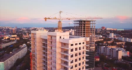 urbanística : Aerial panoramic view of the new high buildings under construction in Vladivostok. Peter the Great Gulf in the Sea of ??Japan with moored ships is on the background. Sunset. Russia