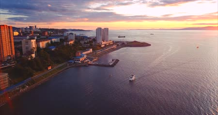 элита : Aerial view of the Great Gulf (sea of ??Japan) and zooming in view of sailing yacht. Vladivostok, Russia. Evening, beautiful sunset